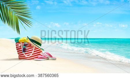 Beach Accessories - Beach Bag, Straw Hat, Flip Flops And Sunglasses On Tropical Beach And Aqua Blue
