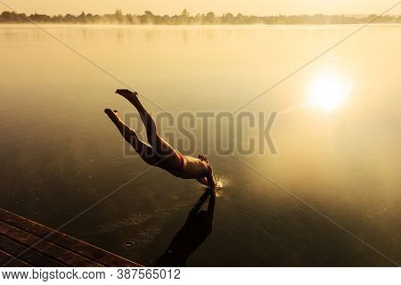 Muscular Sportsman Plunging Into Lake From Wooden Pier