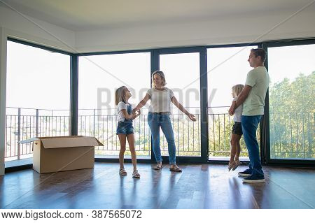 Mother, Father And Two Daughters Standing In Empty Living Room With Open Balcony. Happy Family Reloc
