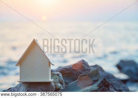 Wooden Miniature Of House On Rock. Sunset Over Ocean. Housing Rental Near Sea Concept. Summer Holida