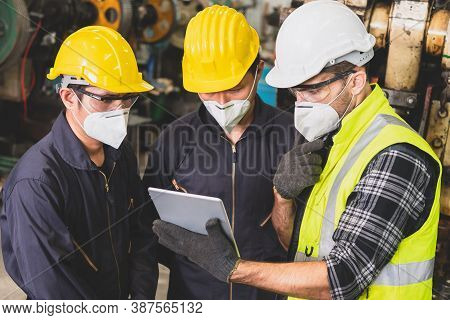 The Factory Engineer In The Hard Hat Is Holding A Tablet Computer To Discuss The Work Detail Inside