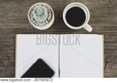 Book, Cactus And Coffee Cup Placed On A Wooden Table, Top View.