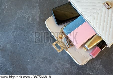 Close-up And Flat Lay Open Beige Bag With Wallet, Lipstick, Hand Cream, Car Key And Smartphone Insid