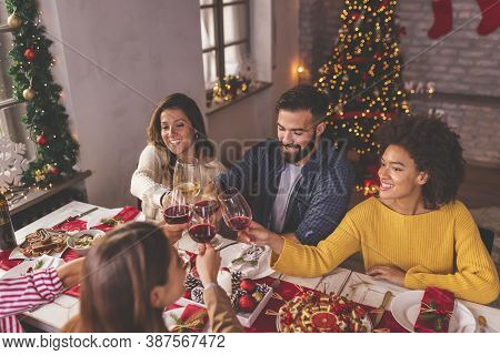 High Angle View Of Group Of Friends Making A Toast During Christmas Dinner, Raising Glasses Of Wine