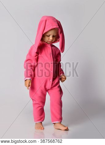 Thoughtful Barefooted Blonde Baby Girl In Pink Warm Jumpsuit With Hood And Bunny Ear Walks Slowly Lo