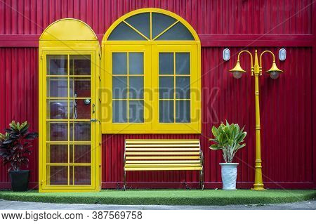 Yellow Telephone Box, Bench And Lamppost On The Background Of A Red Metal Wall On The Street Of Dana