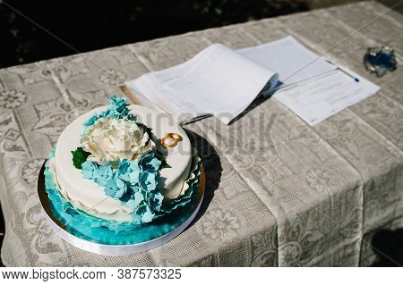 Wedding Cake On The Table Near The Marriage Magazine. Two Golden Wedding Rings On The Background Of
