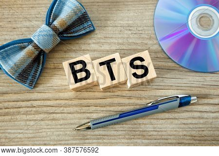 Bts Concept With Wooden Cubes. Bts Word On Cd Background, Bow Tie And Pen