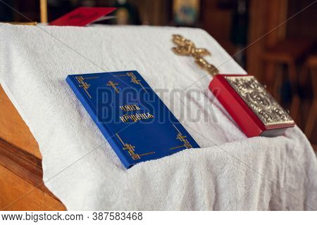 The Sacrament Of Baptism In The Orthodox Church. Prayer Books And A Crucifix On The Table. Inscripti