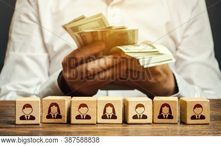 A Man Is Counting Money In His Hands Over Blocks With Symbols Of Employees. Wage Fund. Accounting An