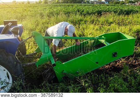 A Farmer Examines A Machine For Digging Out Potato Root Vegetables. Exploitation And Maintenance Of