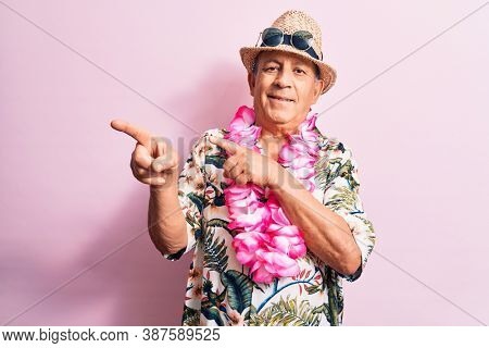 Senior handsome grey-haired man on vacation, wearing summer look with Hawaiian lei flowers smiling and looking at the camera pointing with two hands and fingers to the side.