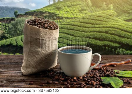 Cup Of Fresh Coffee And Roasted Beans In A Bag On The Table Against The Backdrop Of A Landscape Of C