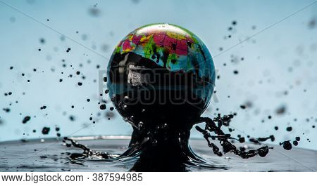 Earth In The Form Of A Globe In The Oil. Concept Of Planet Pollution, Use Of Natural Resources And H