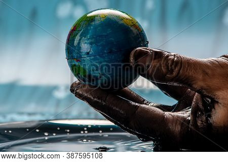 Earth In The Shape Of A Globe In An Petroleum Stained Hand. Concept Of Eco Friendly Behavior And Usi