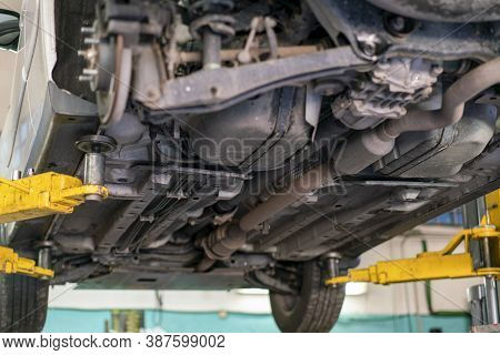 Car Lifted In Automobile Service For Fixing, Worker Repairs Detail, Telephoto. Car Maintenance Shop.