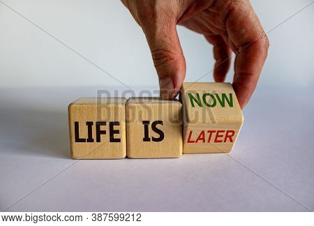 Hand Turns A Cube And Changes The Expression 'life Is Later' To 'life Is Now'. Beautiful White Backg