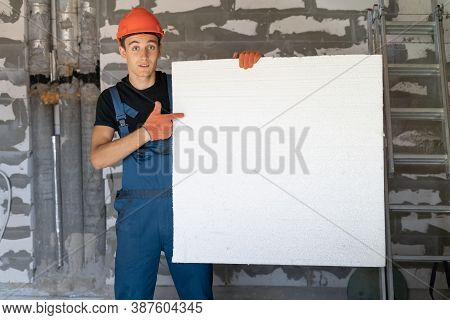 Worker With Helmet Helmet Near A Wall Of Stones. Holding A Large Sheet Of Styrofoam In His Hands. Po