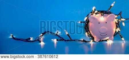 White Piggy Bank With Christmas String Lights On Happy December Festival, Enjoy Savings For Spending