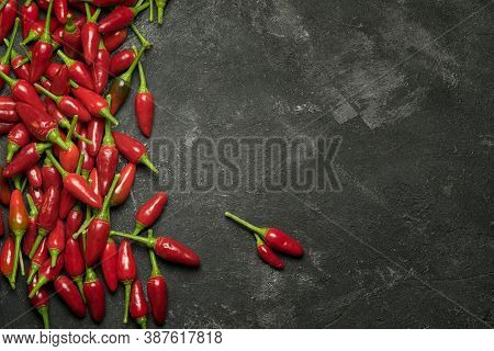 Red Hot Chilli Peppers At The Side, Frame On A Black Table, Top View With Copy Space For Your Culina
