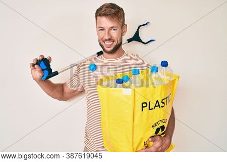Young caucasian man holding recycling bag with plastic bottles and waste picker smiling with a happy and cool smile on face. showing teeth.