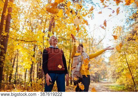 Fall Season. Family Couple Throwing Leaves In Autumn Forest. Senior People Having Fun Outdoors Enjoy