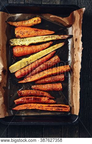 Roasted Carrots In Roasting Tin On A Dark Wooden Background.