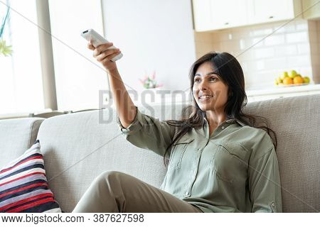 Smiling Happy Young Indian Ethnic Woman Holding Remote Control Turns On Air Conditioner System Relax