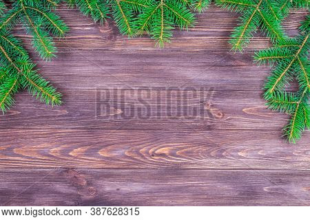 Green Branches Of A Christmas Tree On A Dark Wooden Background. Place For An Inscription. The Basis