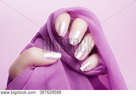Female Hand With Shiny Pink Nails On Pink Background.