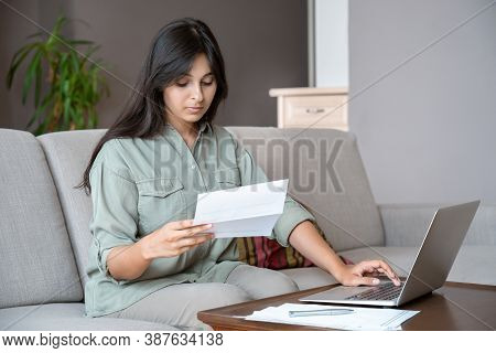 Young Indian Woman Holding Letter Using Laptop Computer Application Paying Bill Online On Website, M