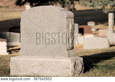 Vintage Stone Headstones On Grave Sites During Late Afternoon Lighting Which Creates Shadows On The