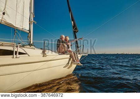 Sailing. Happy Retired Family Couple Sitting On The Side Of A Sail Boat Or Yacht Deck Floating In A