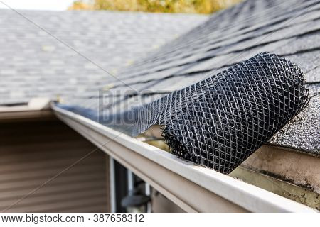 Roll of plastic mesh guard over gutter on a roof to keep it free of leaves, focus on roll of mesh