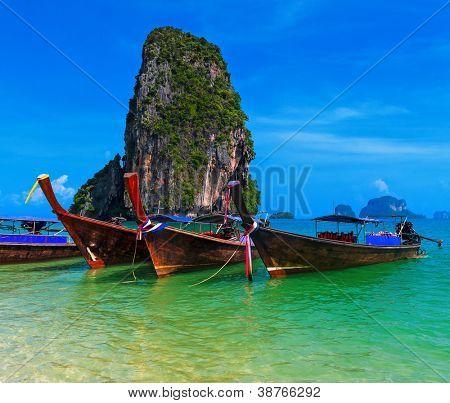 Travel background. Traditional long tail boats in azure sea near Pranang beach, Krabi, Thailand