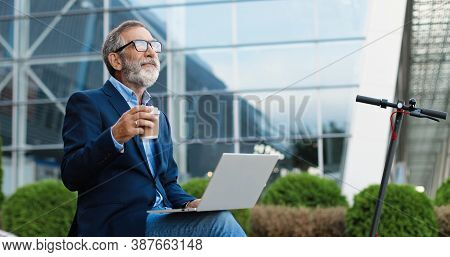 Old Caucasian Man In Glasses Sitting Outdoor At Electric Scooter And Working On Laptop Computer Whil