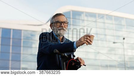 Senior Gray-haired Man In Glasses And Headphones Standing At Bike On Street And Drinking Coffee To-g
