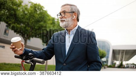 Senior Man In Glasses And Headphones Standing At Electric Scooter On Street, Listening To Music And