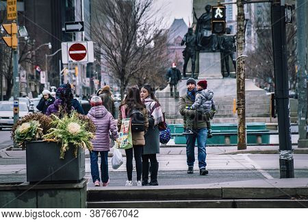 Toronto, Canada - 01 04 2020: Pedestrians Waiting For Traffic Lights In Front Of South African War M