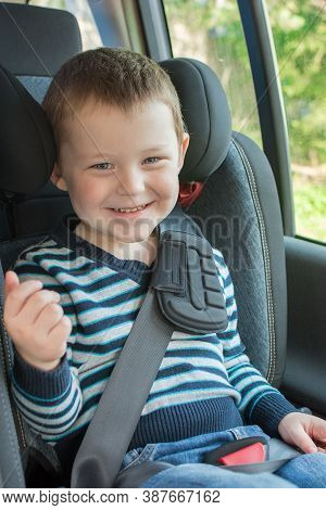 Ittle Boy Sitting In Car Seat, Smiling, Looking At Camera. The Idea Is The Safety And Convenience Of