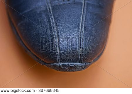 Part On One Black Leather Sneaker On A Blrown Table