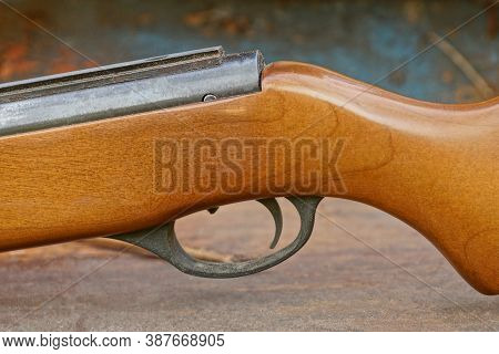 Iron Black Trigger On Brown Rifle On Wooden Table