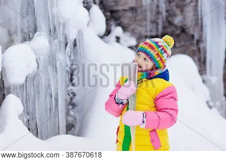 Children Play With Icicle In Snow. Kids Lick Icicles At Frozen Mountain Waterfall On Family Christma