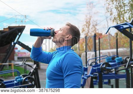 Toned Muscular Man Drinking Whey Protein Cocktail After Workout On The Outdoors Sport Ground. Autumn