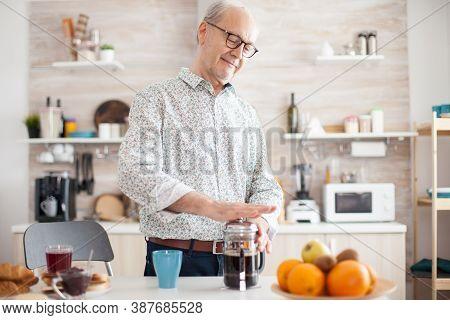 Elderly Retired Man Using French Press For Coffee Preparation In Cozy Bright Kitchen. Senior Person