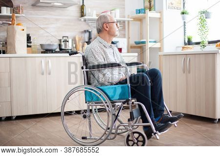 Handicapped Senior Man In Wheelchair Feeling Lonely Looking On The Window. Elderly Handicapped Pensi