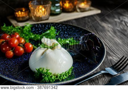 Traditional Italian Dish Of Burrata Stratocell. Burrata On A Dark Plate Is Served For A Romantic Din