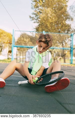 Beautiful Teen Athlete With A Tennis Racket In His Hands. A Tennis Player Sits On The Court And Rest