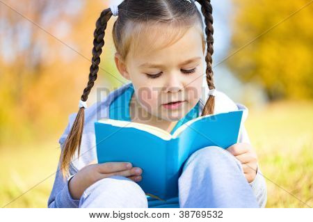 Cute little girl reads a book, isolated over white