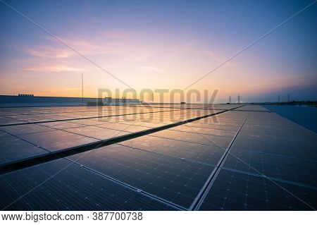 Solar Panel Photovoltaic Install On The Roof Of Factory Under Morning Sky. Solar Cell Alternative El